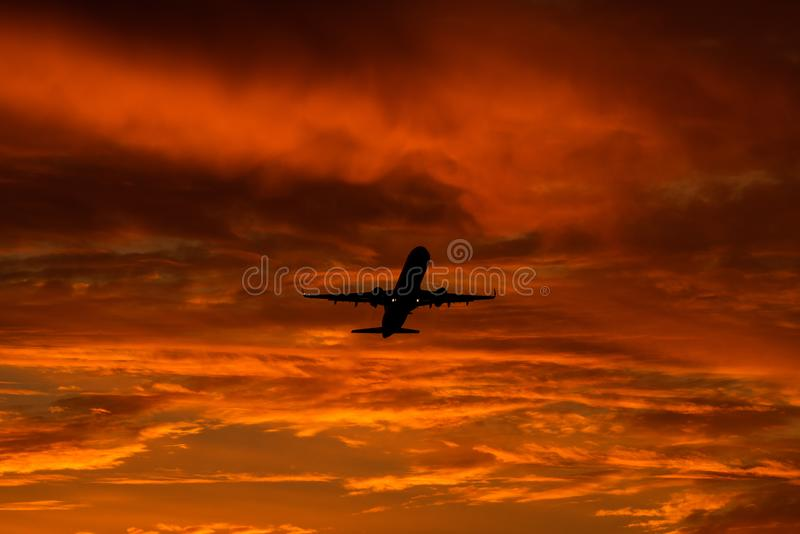 Airplane landing or takeoff in the sunset with red sky in Bucharest international airport , Plain spotting. And aviation photography with sun crossing royalty free stock photography
