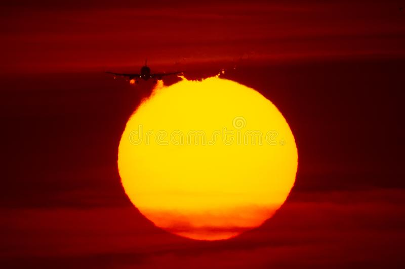 Airplane landing or takeoff in the sunset with red sky in Bucharest international airport , Plain spotting. And aviation photography with sun crossing royalty free stock images