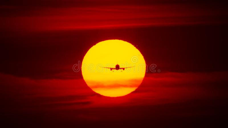Airplane landing or takeoff in the sunset with red sky in Bucharest international airport , Plain spotting royalty free stock photography