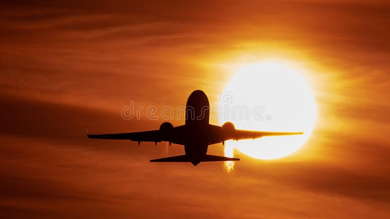 Airplane landing or takeoff in the sunset with red sky in Bucharest international airport , Plain spotting. And aviation photography with sun crossing stock photography