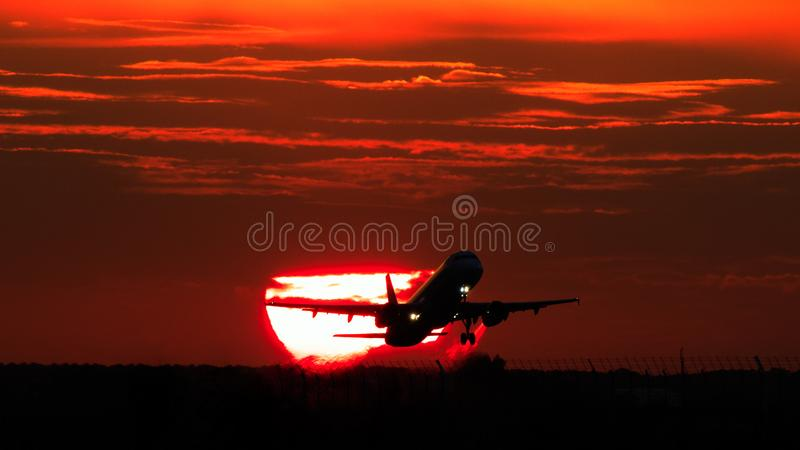 Airplane landing or takeoff in the sunset with red sky in Bucharest international airport , Plain spotting. And aviation photography with sun crossing stock image