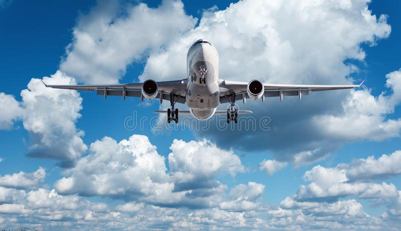 White passenger airplane is flying in the blue sky with clouds stock photos