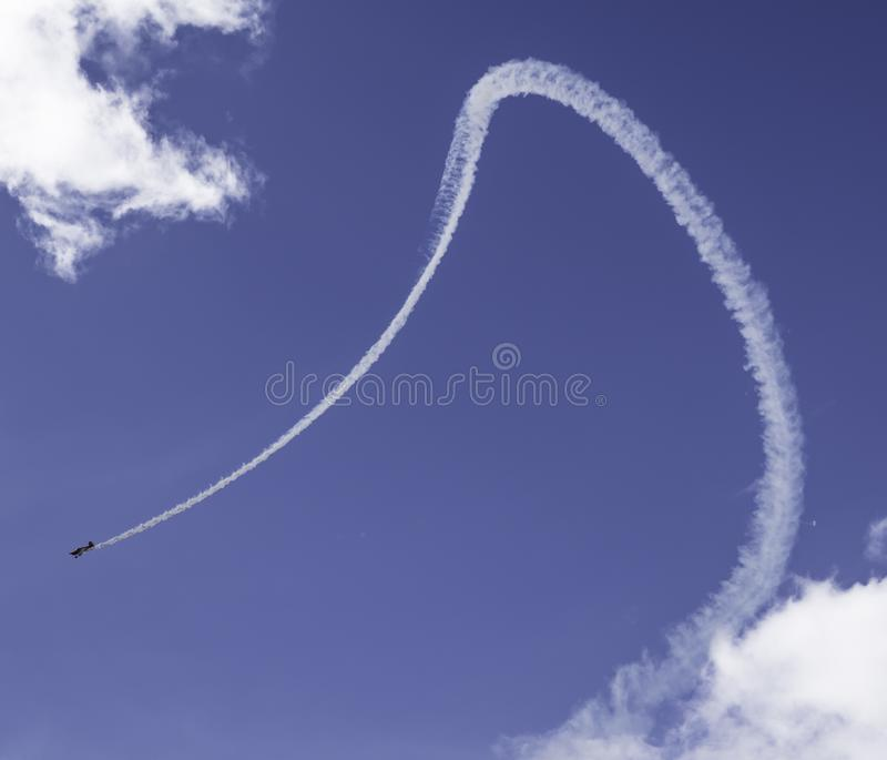 Airplane making contrail. An aeroplane leaving a contrail behind it in an air show royalty free stock images