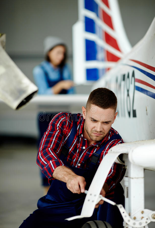 Airplane Mechanic Fixing Chassis stock images