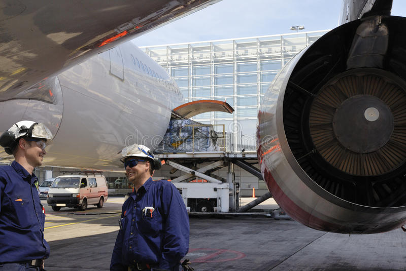 Airplane mechanics and jet engine. Two airplane mechanics, engineers with giant plane and jet engine in background, airport maintenance stock images