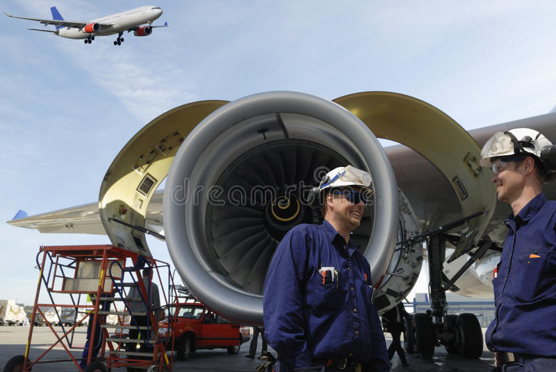 Airplane mechanics and jet-engines. Two aircarft mechanics, engineers, large jet engines in background, airliner coming in for landing stock photo