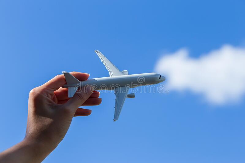 Airplane model in hand on sunny sky. Concepts of travel, transportation royalty free stock photography