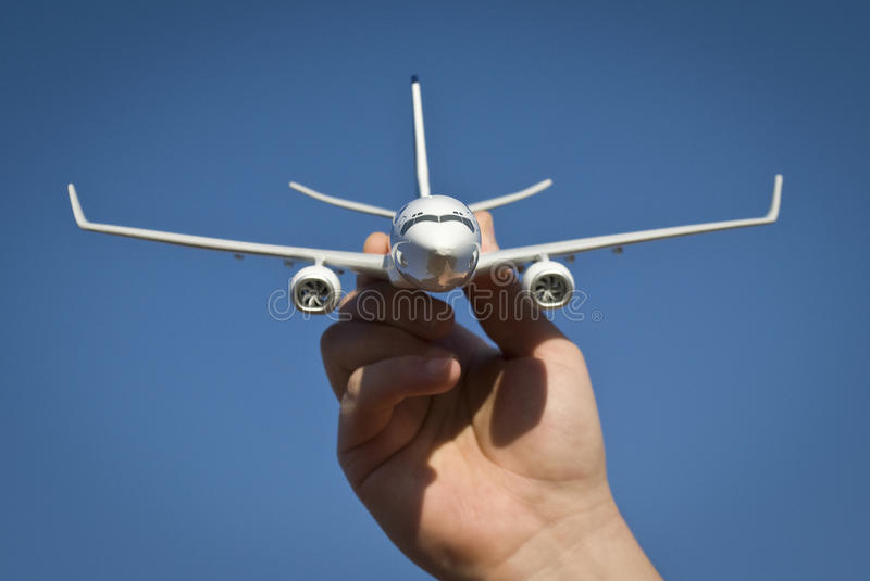Airplane model. White airplane model on blue background held by mans hand stock images