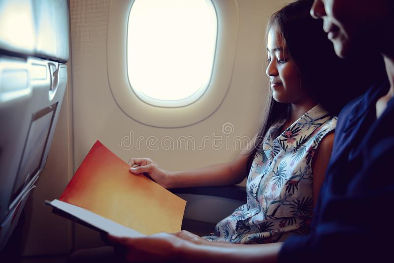 In the Airplane. Mother with daughter sit on their place in airplane economy class and read a magazine royalty free stock photography