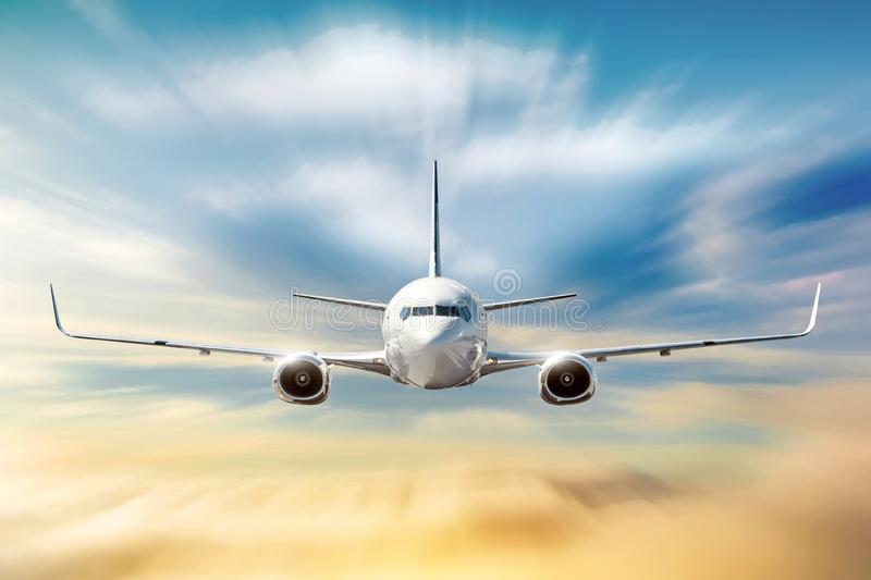 Airplane with motion blur effect is flying in orange clouds at sunset. Concept aviation air transport.  stock photo
