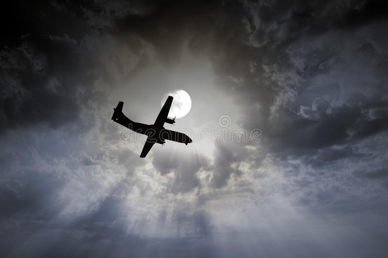 Airplane night flight. Flight of a propeller plane in a full moon night with clouds and rays during landing royalty free stock photography