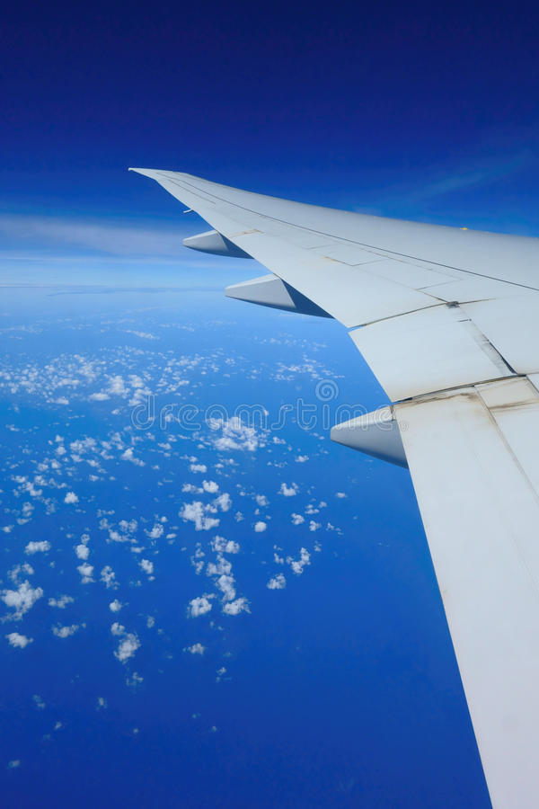 Airplane over clouds stock images