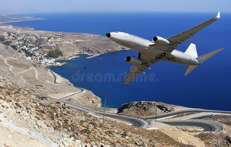 Airplane over seashore royalty free stock photos