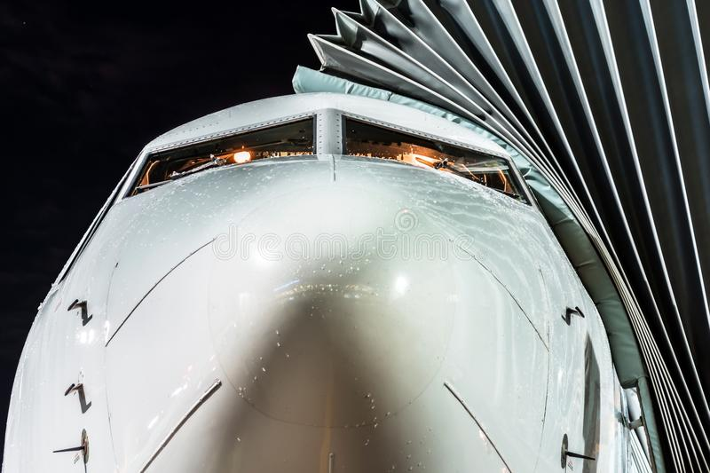 Airplane parked at the airport at night, view nose cockpit close up. royalty free stock photo