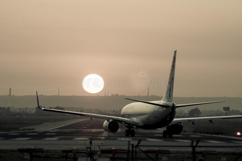 Airplane photographed from behind landing at Seville airport at sunset royalty free stock photos