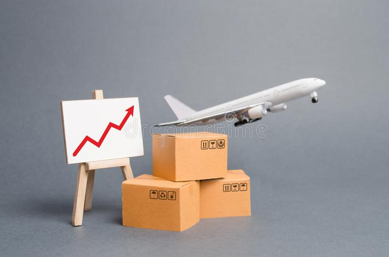 Airplane plane takes off behind stack of cardboard boxes and stand with red up arrow. concept of air cargo and parcels, airmail. Fast delivery of goods and royalty free stock photos