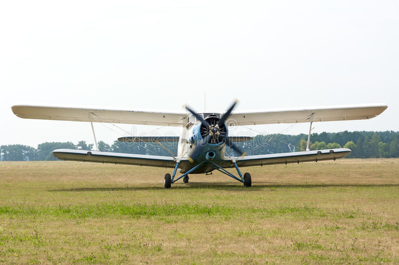 AN2 airplane with rotating propeller. AN2 plane with the engine running and rotating before take off from the field aerodrome. Summer day in the sky overcast royalty free stock images