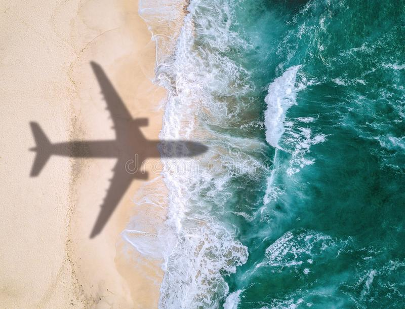 Airplane`s shadow over beach stock photography