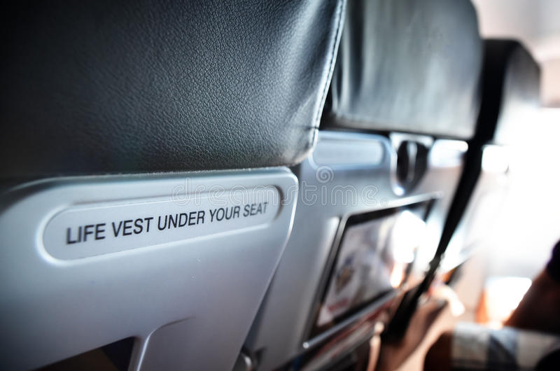 Airplane seat. With life vest under your seat text stock photos