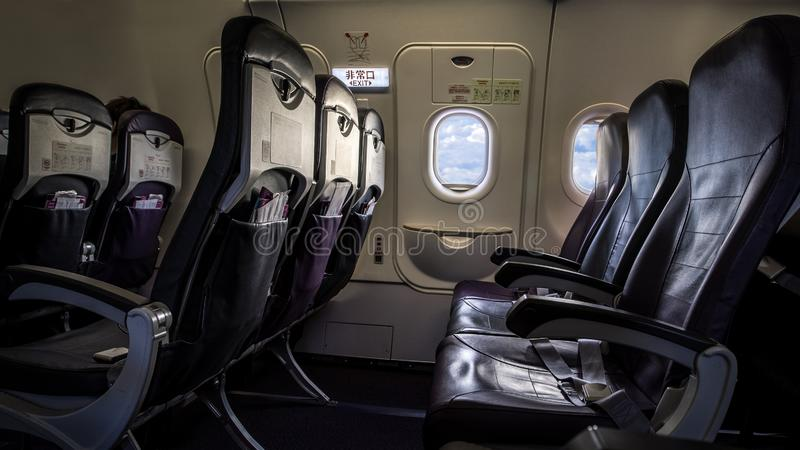 Airplane seat and windows inside an aircraft. Clouds airplane passenger window royalty free stock photos