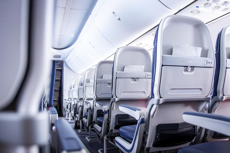 Airplane seats in cabin. Commercial aircraft cabin with rows of seats down the aisle. Economy class. Airplane seats in cabin. Commercial aircraft cabin with stock photography
