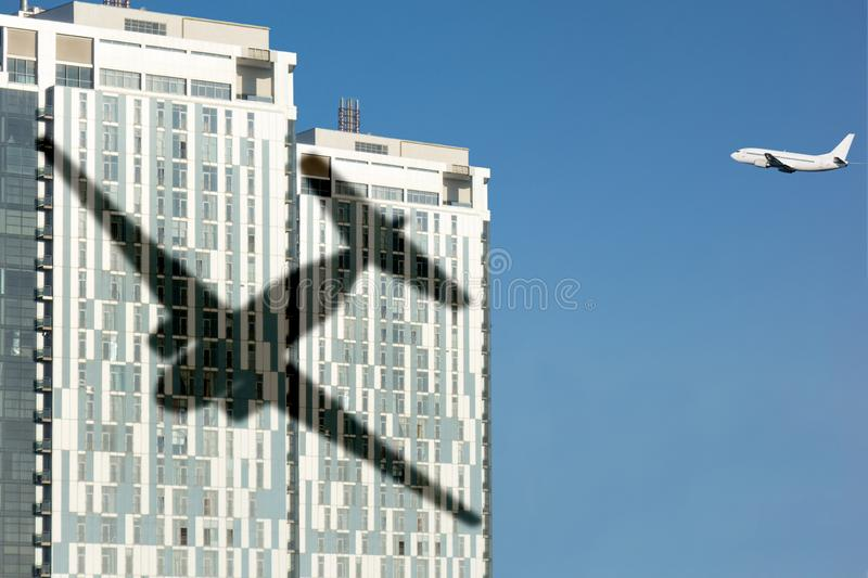 Airplane shadow on skyscraper building. Concept of aviation safety or airport close living. Noise reduction in modern urban royalty free stock photo