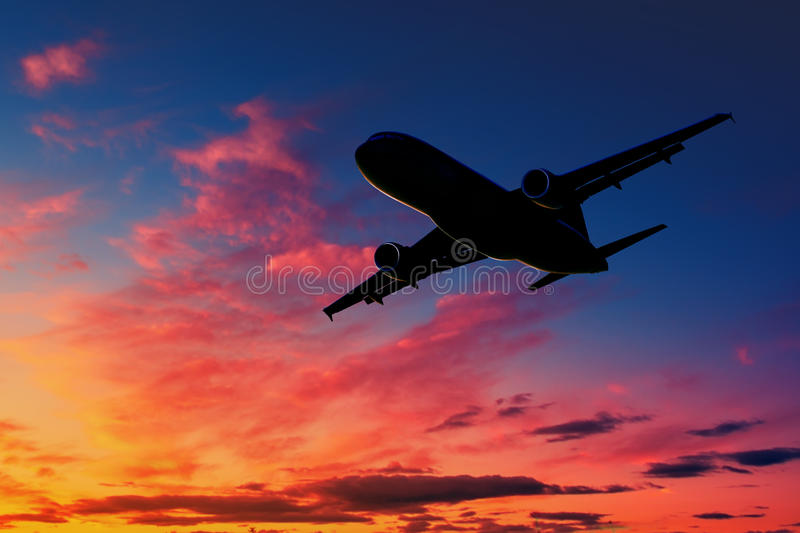 Airplane silhouette in the sky at sunset stock photo