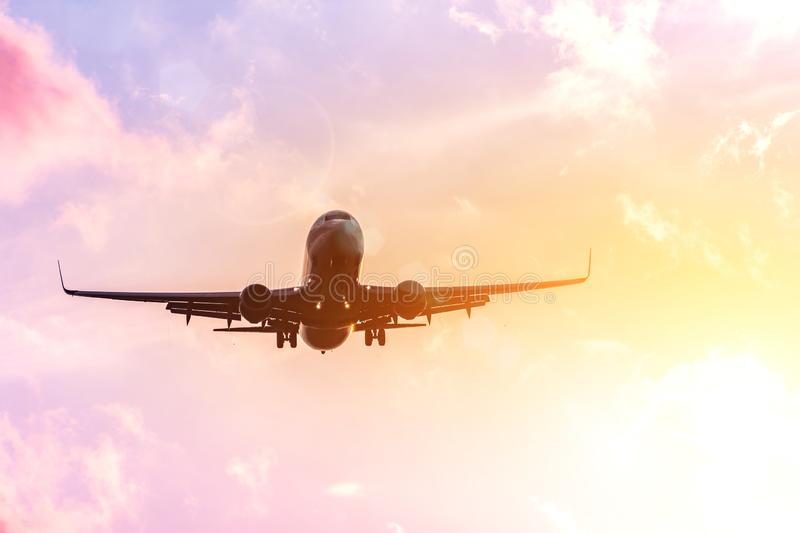 Airplane silhouette in warm in the yellow-pink tones of the sky and clouds. Copcept travel to warmer countries.  royalty free stock photos
