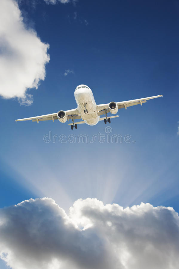 Airplane in the sky. Large passenger airplane flying in the blue sky royalty free stock image
