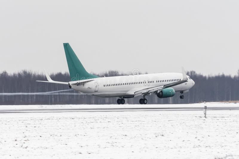 Airplane take off from the snow-covered runway airport in bad weather during a snow storm, a strong wind in the winter. Airplane take off from the snow-covered royalty free stock image