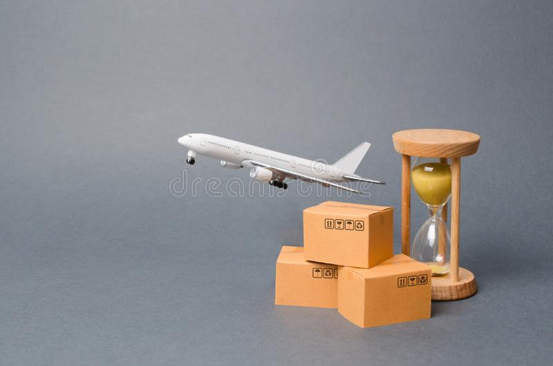 Airplane takes off behind the stack of cardboard boxes and a sand clock. concept of air cargo and parcels, airmail. Fast delivery. Of goods and products. Cargo royalty free stock images