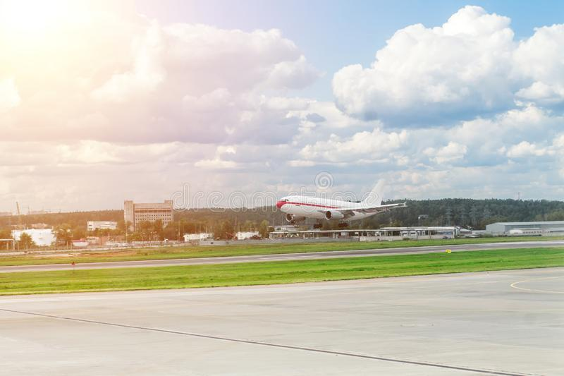 Airplane taking off from the airport. white with red stripe passenger plane on sunny day.  royalty free stock photos