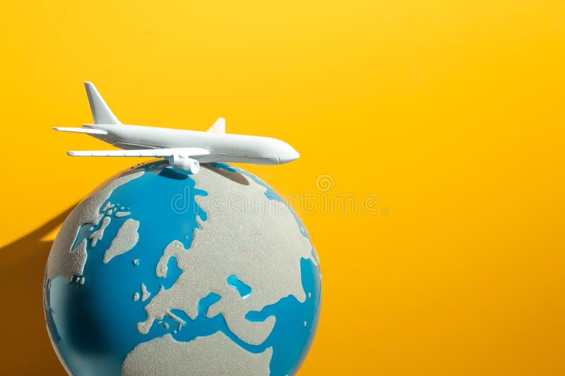 Airplane toy model with global world map on yellow background in transportation business for travel tourist international concept,. Summer season holiday stock photo