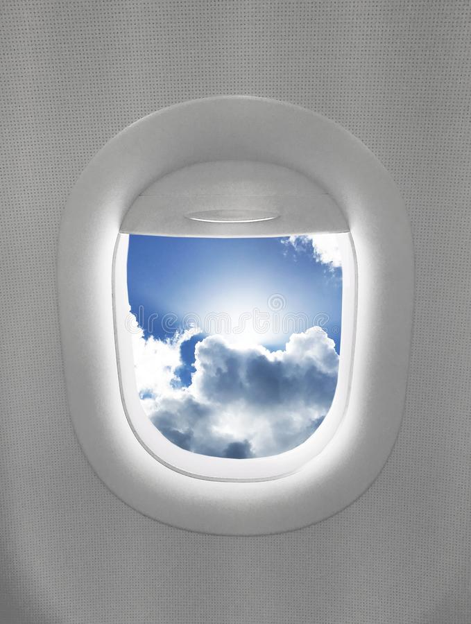 Airplane Window Blue Sky Clouds Isolated. Airplane window with bright blue sky and clouds with sun peaking out solo isolated art print travel royalty free stock photos