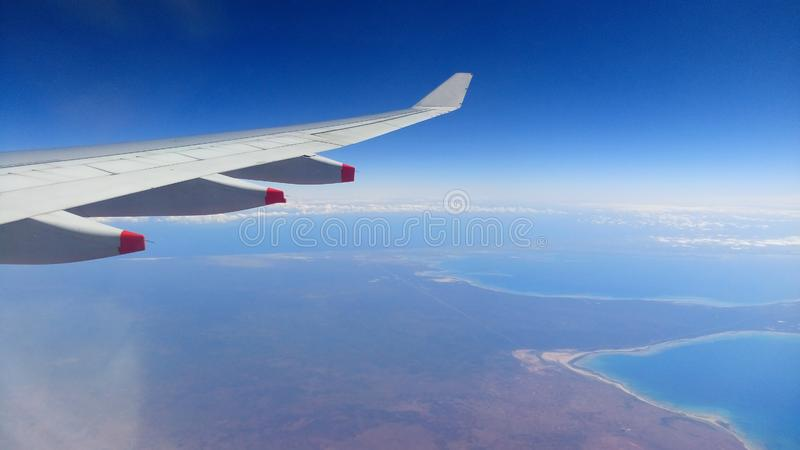 Airplane Window Seat -with beautiful view of wing of plane on flight and  traveling in air over city and clouds. Airplane Window Seat -with beautiful view of stock photo