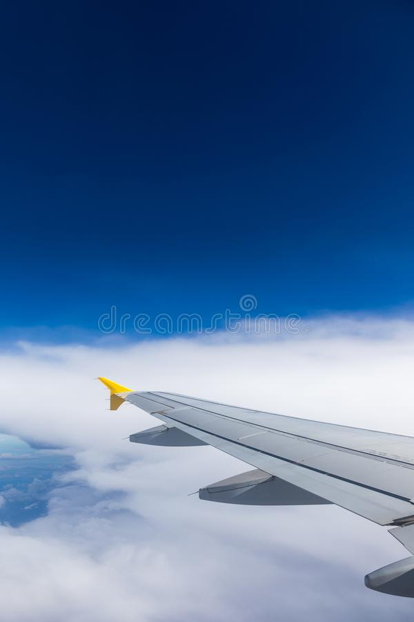 Airplane windows view above the earth on landmark down. View from an airplane window over a wing flying high above farmlands and royalty free stock photos
