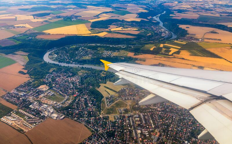 Airplane windows view above the earth on landmark down. View from an airplane window over a wing flying high above farmlands and royalty free stock photo