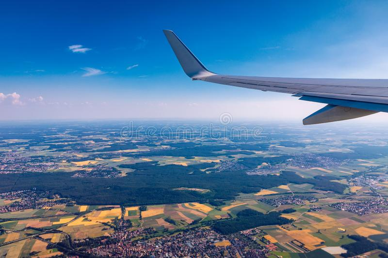 Airplane windows view above the earth on landmark down. View from an airplane window over a wing flying high above farmlands and royalty free stock image