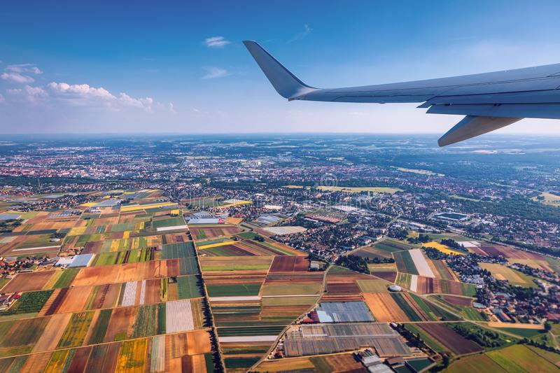 Airplane windows view above the earth on landmark down. View from an airplane window over a wing flying high above farmlands and royalty free stock images