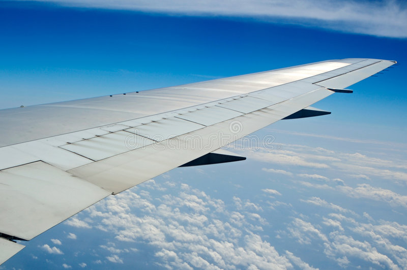 Airplane wing. In the blue sky with white clouds stock images