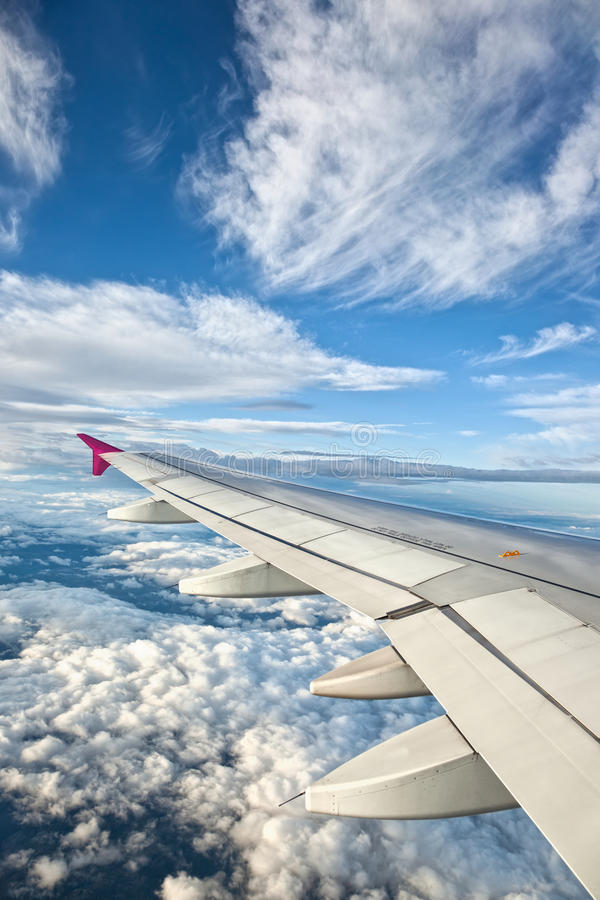 Airplane Wing. Against Blue Sky and Clouds stock photography