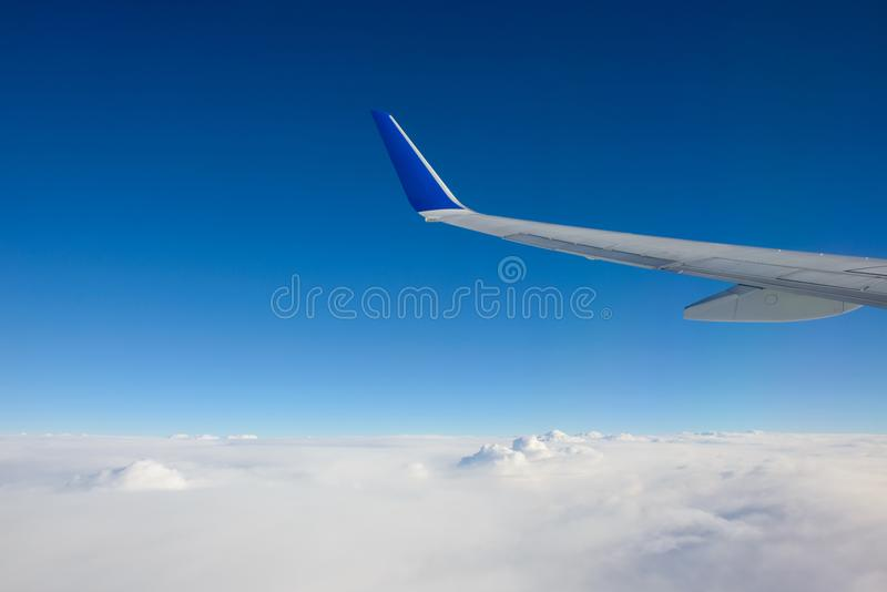 Airplane wing with blue sky has a lot of windows stock photos