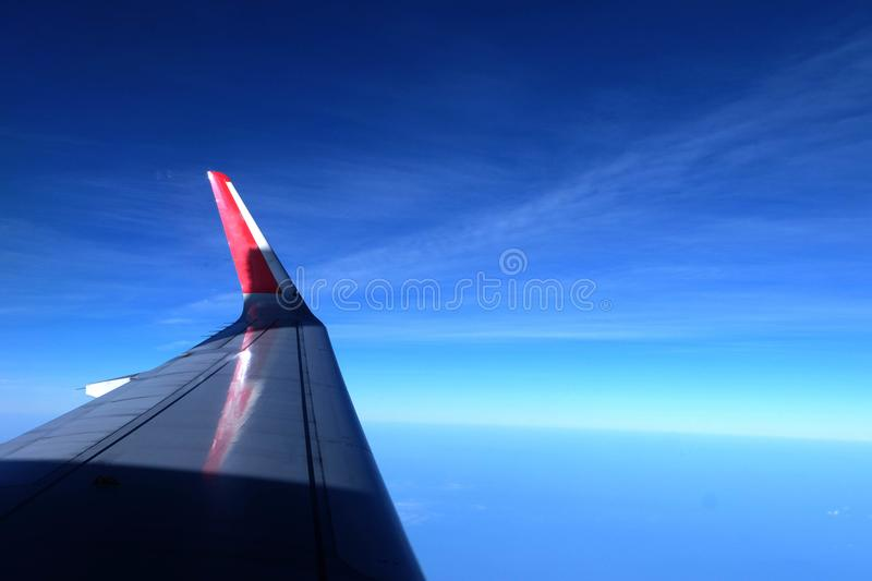 Airplane wing in the sky. The airplane wing in the blue sky, travel on the beautiful and safe trip royalty free stock images