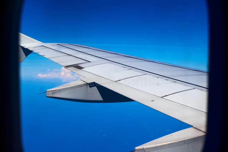 Airplane wing in blue sky, view through plane window. Travel by air. Aircraft window view. royalty free stock photography
