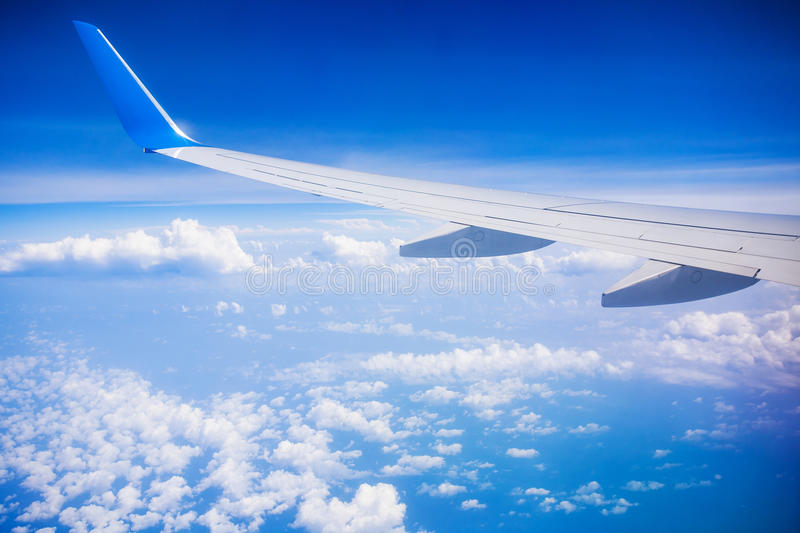 Airplane wing with blue sky and white clouds stock images