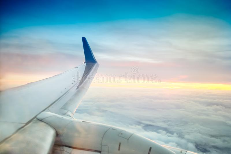 Airplane wing flying above clouds on the sunset. Selective focus. Space for text stock photography