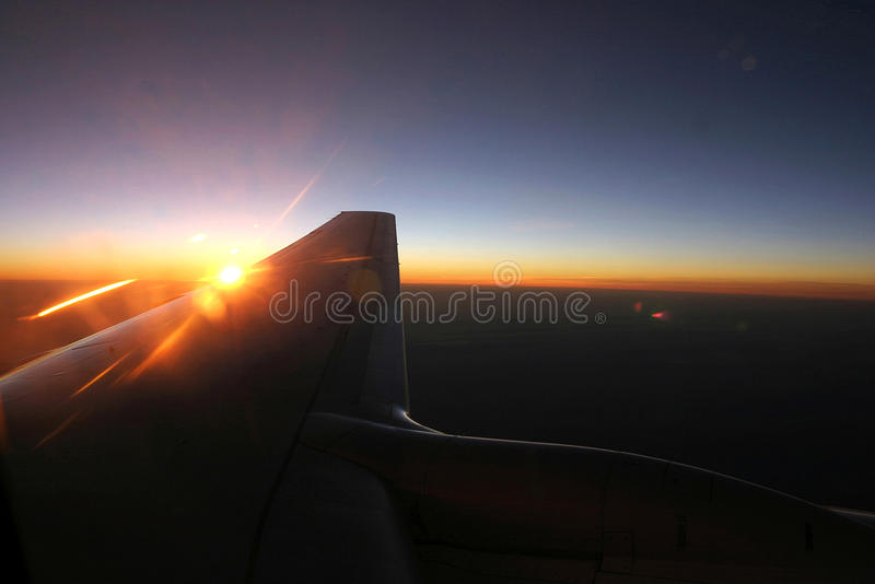 Airplane wing flying over clouds when view from window at sunset stock photos
