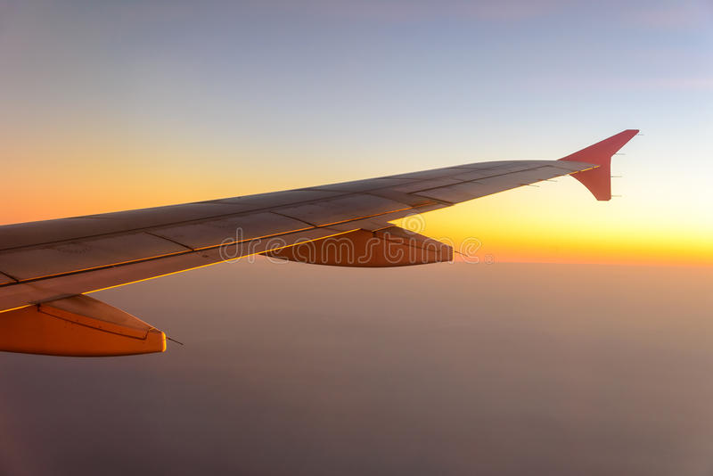 Airplane wing. Flying in the sunset royalty free stock images