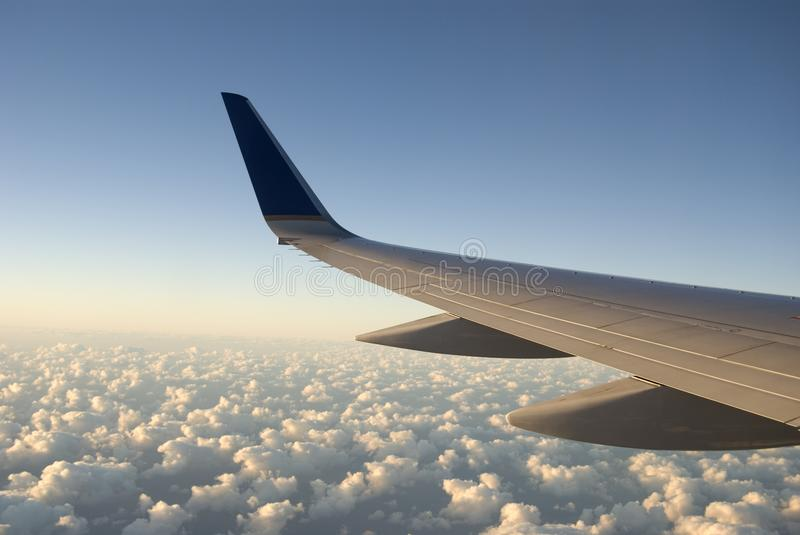 Airplane Wing over Clouds Viewed form the Cabin. Horizontal Image of Airplane Wing over Clouds Viewed form the Cabin stock photo