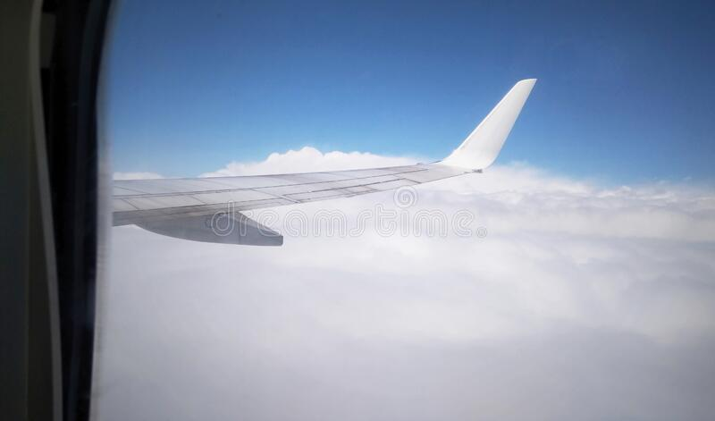 Airplane wing from plane window. View from the aircraft`s airplane to the wing in the sky above the clouds. Flight by plane.  stock photos